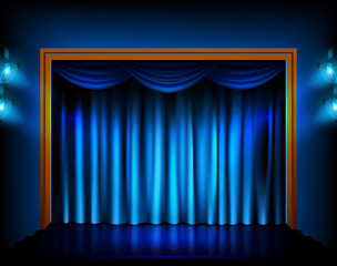 Theater stage with blue curtains and spotlights.