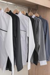 shirts hanging on rail in modern wooden wardrobe