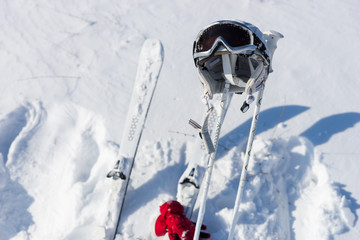 Helmet, Goggles, Poles and Skis on Snowy Hillside