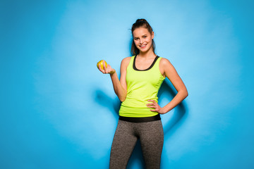 pretty woman in sport equipment holding an apple in hand