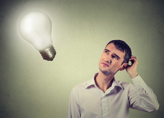 concerned man thinks looking up at light bulb
