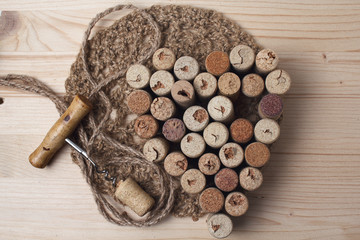 Heart laid out from bottle corks and corkscrew on wooden backgro