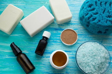 natural organic soap bottles essential oil and sea salt herbal bath  on a blue wooden table