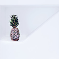Pineapple in pink paint in white interior. Minimalism fashion