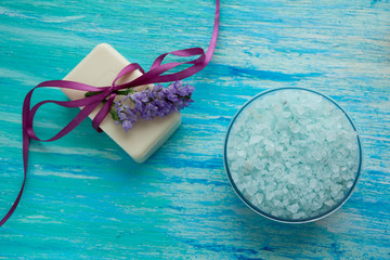 natural organic soap, and sea salt with flowers on a blue wooden