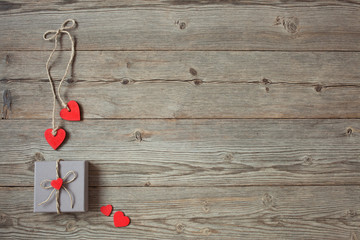 Wooden background with a gift in a box and red hearts on Valentine's Day