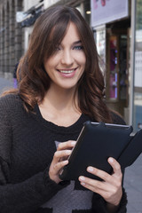 Young woman holding a tablet on the street