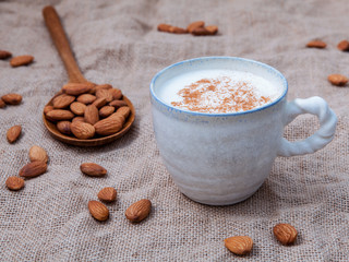 Homemade almond milk in the coffee cup with almond in the wooden