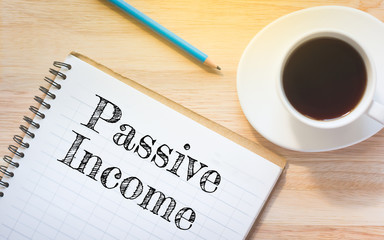 Concept Passive Income message on book. A pencil and a glass coffee table.Vintage tone.