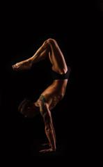 muscular man practicing yoga and gymnastics, handstand
