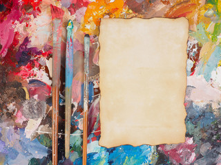 Brush and paper on oil-paint palette for background