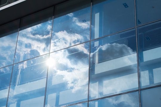 Sun ray and blue sky reflection on window office building, Busin
