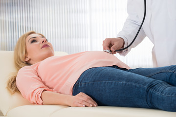 Doctor Examining Pregnant Woman With Stethoscope