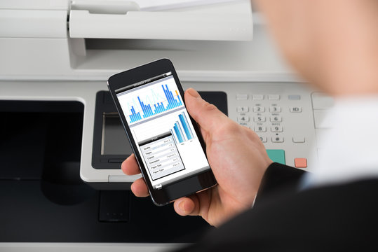 Businessman Giving Print Command On Smart Phone