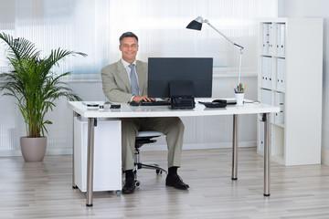 Smiling Businessman Using Computer At Desk