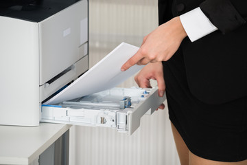 Businesswoman Inserting Papers In Photocopy Machine