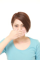 young Japanese woman making the speak no evil gesture