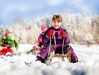 Happy children sledding at winter time. Group of children spending a nice time in snowy mountain