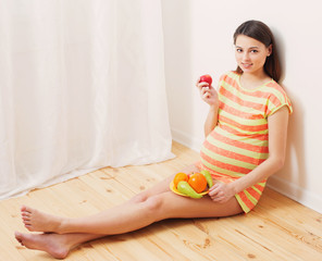 Pregnant woman eating fruits