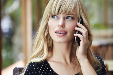 Wall Mural - Blue eyed young blond woman on Smartphone