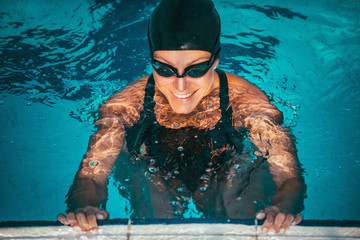 Smiling swimmer at the pool edge