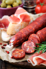 Spanish tapas - slices chorizo, jamon serrano, olives and bread