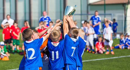 Young Sport Team with Trophy. Boys Celebrating Sports Achievement. Young Soccer Players Holding Trophy. Celebrating Soccer Football Championship. Winning team of sport tournament for kids children.