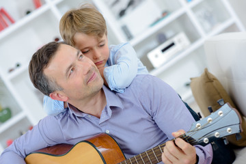 Man playing guitar, boy leaning on his shoulders