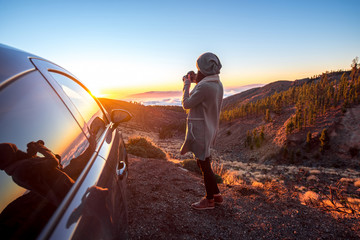 Woman photographing landscape standing near the car