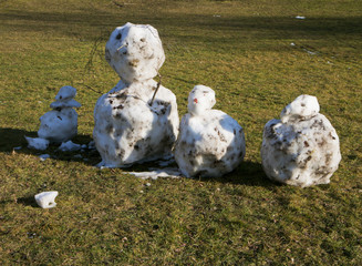 snowmen made with snowballs and decorated by twigs on a sunny day over a green field