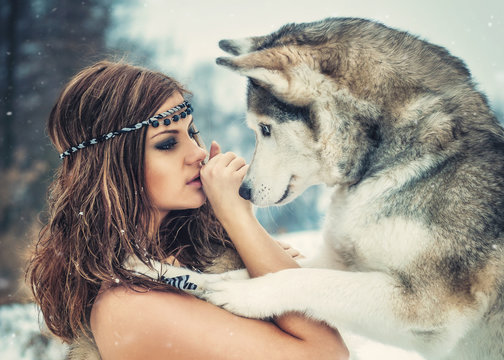 Friendship/ Delightful girl plays with a Siberian Husky in snowy woods