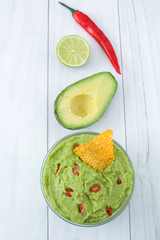 Guacamole with nachos, chili peppers