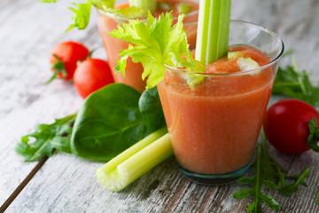 Fresh smoothies tomato and celery on a  wooden background