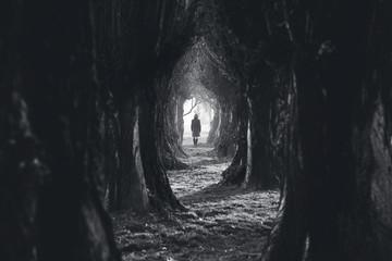 Woman walking in the dark deep forest