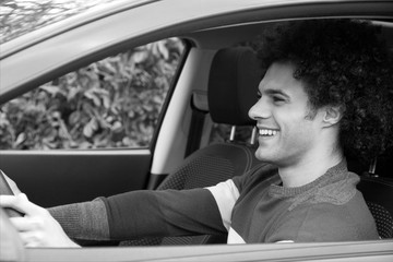 Smiling man driving new car happy black and white
