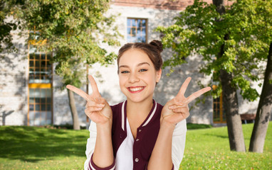 happy teenage student girl showing peace sign