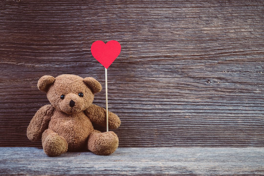 Teddy bear with heart sitting on old wood background.