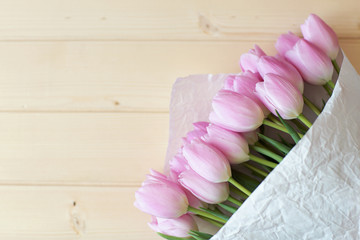 bouquet of pink tulips lie on natural wooden textur table wrapped in Kraft paper