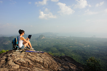 young woman backpacker sit on mountain peak rock use digital tablet