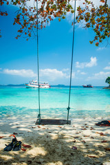 Swing in a perfect beautiful paradise beach with a ship, tourist