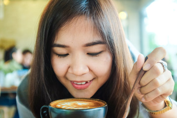 Beautiful cute asian girl in the art cafe  with coffee smiling