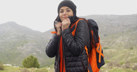Young active woman hiking on a mountainside with her backpack in winter snuggling into her warm anorak with a smile against a cold landscape