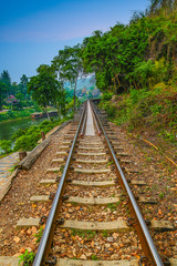railway, death railway the railway of history of world war in forest with blue sky and humid green leaf tree
