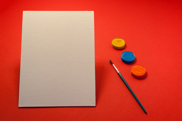 Close up White Blank Canvas mock up with paintbrush and painting colors on red background
