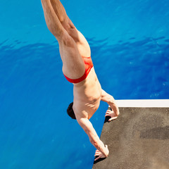 Wall Murals Diving High diving competitor, starting a difficult dive from handstand. Shot from above