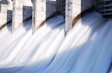 Water rushing out of opened gates of a hydro electric power dam in long exposure Wall mural