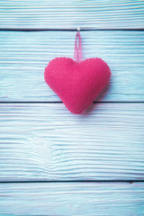 Rosy heart over light blue wooden background