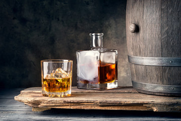 Photo sur Plexiglas Bar Glass of whiskey with ice decanter and barrel