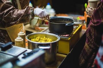 Man preparing vegetarian food, fast food in the evening, the seller prepares porridge