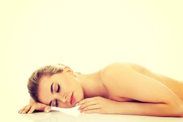 Beautiful naked woman lying on the floor.